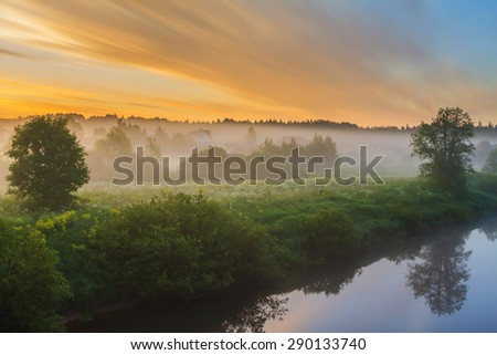 Dawn bright clouds over the village at the river. Early twilight outdoors. Sunrise in Russia. Foggy morning in the village at the river. Sunrise on the river bank in the village. Bright fine sunrise.  - stock photo