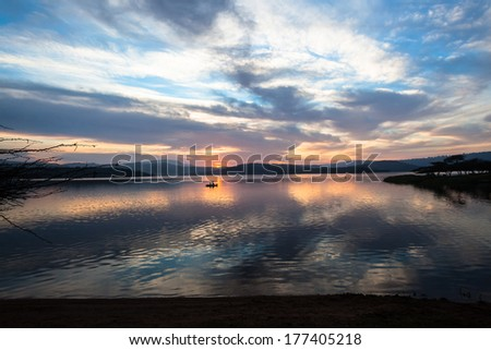 Dawn Colors Dam Waters Fishing  Dawn nature's color reflections over dam smooth waters sky clouds landscape with distant fishing boat   - stock photo