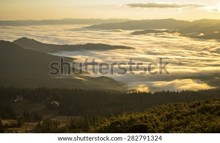 Dawn in the mountains above the clouds and the village - stock photo