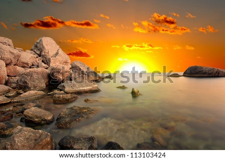 Dawn on the sea. The rising sun on the background of the sea and cliffs - stock photo