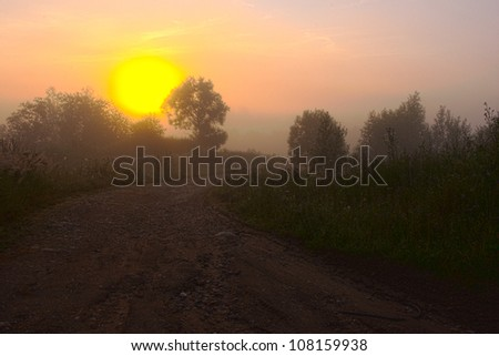 dawn over the road in a morning fog - stock photo