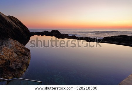 Dawn skies at the Blue Pool in Bermagui, a natural rock pool full of sealife including sea hares, bubble snails and starry sea stars - stock photo