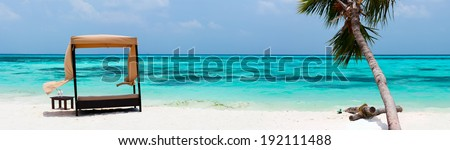 Day bed cabana on a beautiful tropical beach with a palm tree at Maldives - stock photo