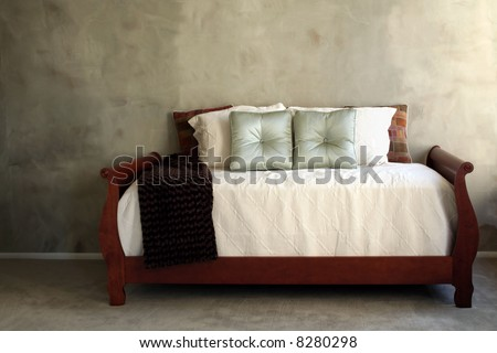 Day bed with cream linens against green textured wall