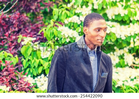 Day Dream. A young black college student standing outside by green, purple, white plants, looking down, thinking, making funny face, smiling. Concept of teenager self esteem. Instagram filtered look.  - stock photo