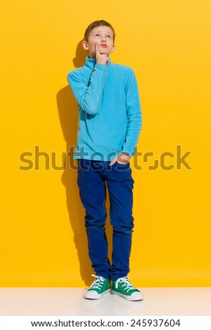 Day dreamer. Thinking young boy standing and holding index finger on a chin. Full length length studio shot on yellow background. - stock photo