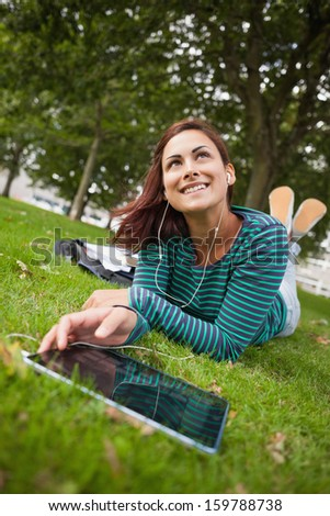 Day dreaming casual student lying on grass using tablet on campus at college