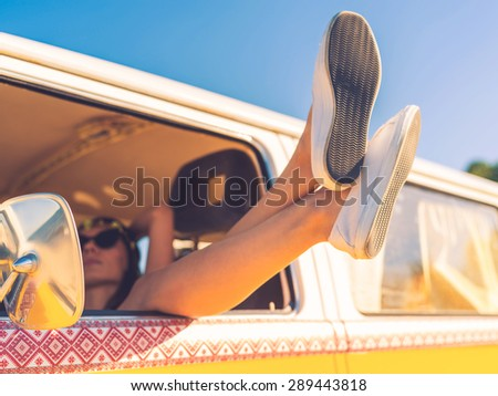 Day dreaming in car. Close-up of young woman holding legs out of the window while sitting inside of minivan - stock photo