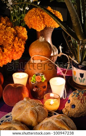 Day of the dead offering altar (Dia de Muertos) Celebration with bread ¨Pan de Muerto¨ chocolate and amaranto skulls and flowery in background. - stock photo