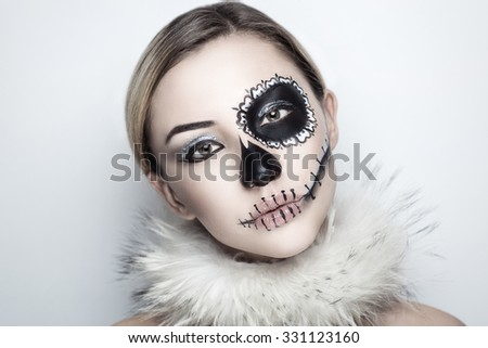 Day of the Dead, Skull Mask. Art woman beautiful face painted as a traditional day of dead, white fur. Free place on photo for congratulations. Good for Halloween card, present, banner, advertisement - stock photo