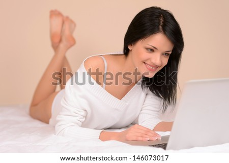 Day off at home. Beautiful young woman using computer while lying on the sofa