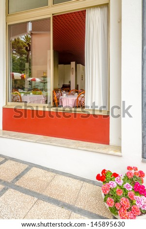 Day view of a hotel exterior with window to dining room. - stock photo