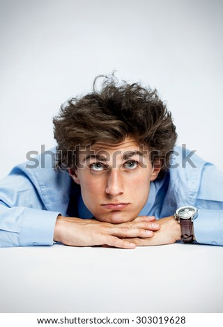 Daydreamer / photos of young man resting his chin on his hands, laying on a table and looking upwards over gray background - stock photo
