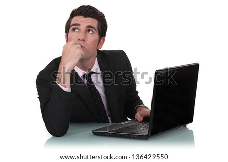 Daydreaming businessman sat at his desk - stock photo