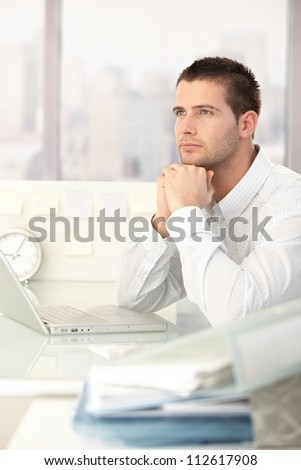 Daydreaming businessman sitting at desk in bright office. - stock photo