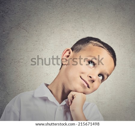 Daydreaming child. Portrait, headshot thinking child, chin on hand, looking up, smiling isolated grey wall background. Positive human facial expressions, emotion, feeling, life perception, imagination - stock photo