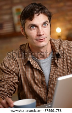Daydreaming man sitting at table, looking up. - stock photo