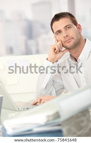 Daydreaming young man sitting at desk with lots of folders.? - stock photo