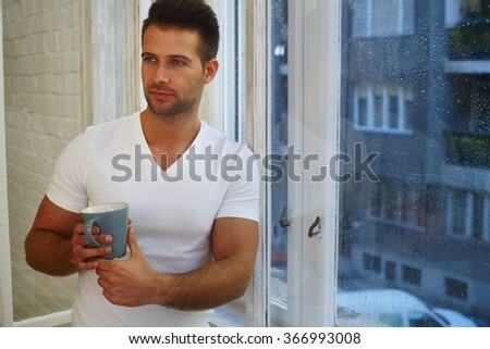 Daydreaming young man standing front of window in rainy morning, holding mug of tea. - stock photo