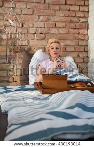 Daydreaming young woman drinking tea in bed in the morning. - stock photo