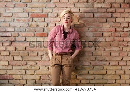 Daydreaming young woman standing over brick wall in retro clothes. - stock photo