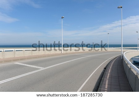 Daylight shot of a curving road in Barcelona, Spain, with sea on the background.Daylight shot of a curving road in Barcelona, Spain. - stock photo