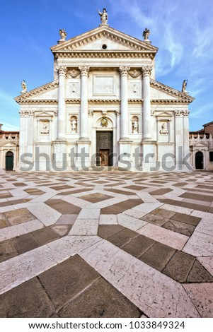 Daylight view from bottom to front facade of San Giorgio Maggiore church with entrance. Bright blue sky with clouds on background. Negative copy space, place for text. Venice, Italy