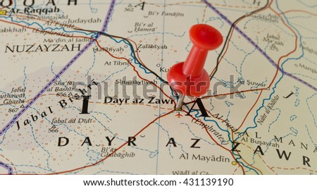 Dayr Al-Zawr marked on map with red pushpin. Selective focus on the word Dayr Al-Zawr and the pushpin. Pin is in an angle. Midground is sharp while foreground and background is blurry. - stock photo