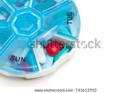 Days of the week pill container with medication isolated on a white background