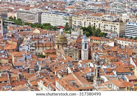 Daytime cityscape of historic Nice in French Riviera with red roofs of the old town, churches and parks - stock photo