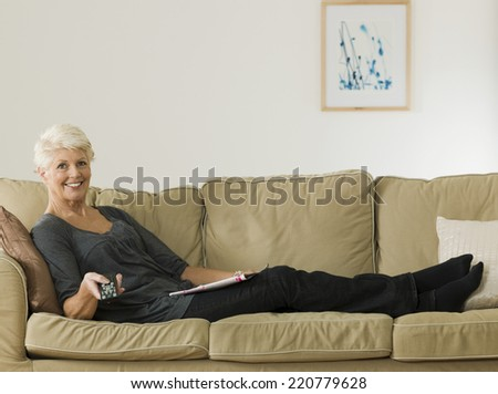 Daytime scene of a senior woman lying on a sofa watching television - stock photo