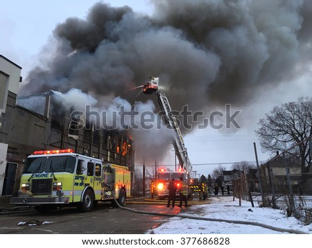 DAYTON, OHIO - FEBRUARY 16: Fire Department sprays water onto roof of condemned Industrial Building fire in Dayton, Ohio on February 16, 2016. - stock photo