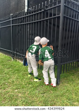 DAYTONA BEACH , FL - JUNE 9: Two young Little League players try to catch a glimpse of the minor-league players in the batting cage at the Jackie Robinson Stadium. - stock photo