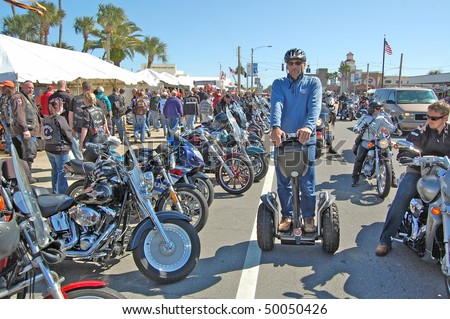 "DAYTONA BEACH, FL - MARCH 6:  A lone Segway glides down Beach Street amid the sea of bikers in town for ""Bike Week 2010"" in Daytona Beach, Florida. - stock photo"