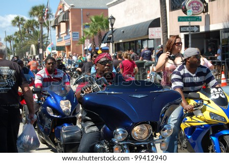 "DAYTONA BEACH, FL - MARCH 17: African-American bikers cruise Main Street during ""Bike Week 2012"" in Daytona Beach, Florida."