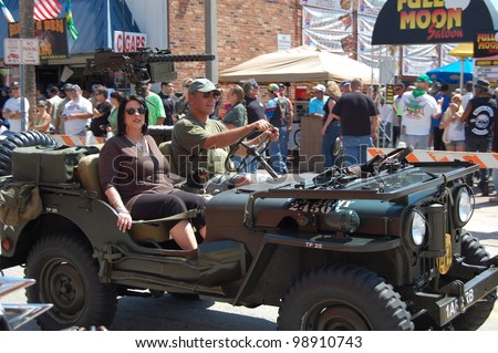 "DAYTONA BEACH, FL - MARCH 17:  An unidentified couple and their dog cruise down Main Street in a U.S. Army jeep during ""Bike Week 2012"" in Daytona Beach, Florida."