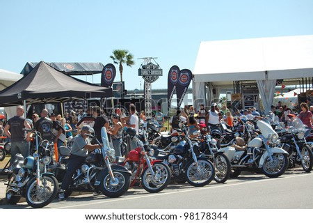 "DAYTONA BEACH, FL - MARCH 17: Bikers check out the vendors downtown during ""Bike Week 2012"" in Daytona Beach, Florida. March 17, 2012 - stock photo"