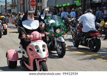 "DAYTONA BEACH, FL - MARCH 17:  Bikers get creative as they cruise Main Street dressed like nuns during ""Bike Week 2012"" in Daytona Beach, Florida. - stock photo"
