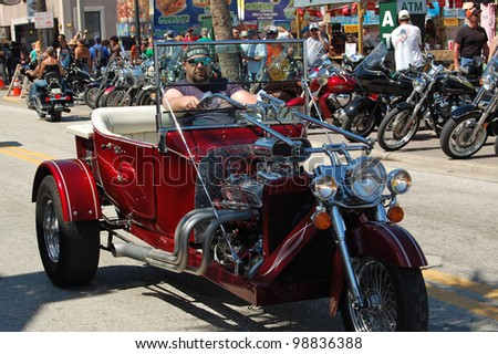 "DAYTONA BEACH, FL - MARCH 17:  Customized motorcycles cruise Main Street during ""Bike Week 2012"" in Daytona Beach, Florida."