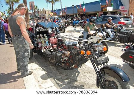"DAYTONA BEACH, FL - MARCH 17:  Customized motorcycles line Main Street during ""Bike Week 2012"" in Daytona Beach, Florida. - stock photo"