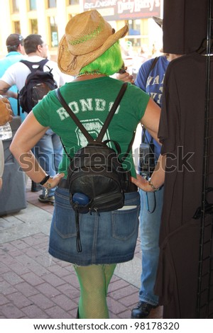 "DAYTONA BEACH, FL - MARCH 17:  Spectators celebrate St. Patrick's Day on Main Street amid the sea of bikers in town for ""Bike Week 2012"" in Daytona Beach, Florida. March 17, 2012 - stock photo"