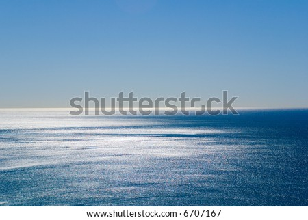Dazzling silver reflections of light off the pacific ocean under a perfect blue sky. Plenty of space for Copyspace