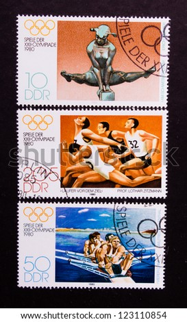 DDR - CIRCA 1980: A stamp printed in DDR shows sportsmen who jump,run and swim, circa 1980.