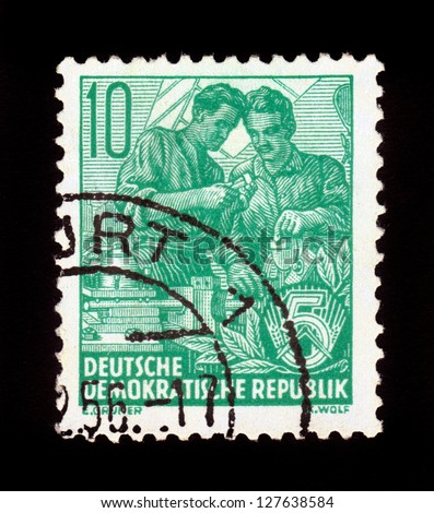 "DDR - CIRCA 1958: A stamp printed in GDR (German Democratic Republic - East Germany) shows exchange of experience working between two workers , series "" workers for the five year plan "", circa 1958"