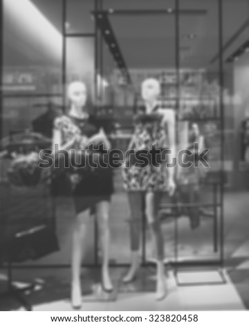 De focused/Blur, black and white image of boutique window with dressed mannequins. Boutique display window with mannequins in fashionable dresses.  - stock photo