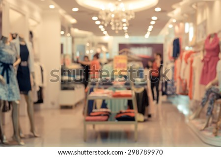 De focused/Blur image of a dress store with customers and dressed mannequins.  - stock photo