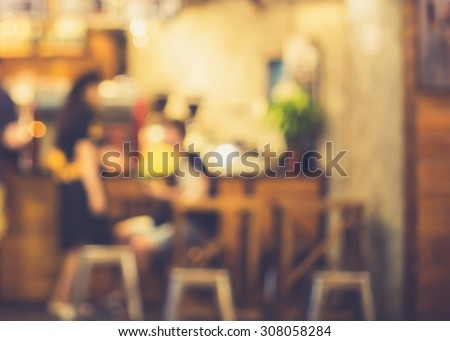 De focused/Blur image of a girl standing and a boy sitting in front of a open cafe. Blurred people in cafe. Retro effect.  - stock photo