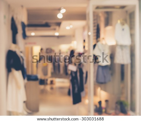 De focused/Blur image of boutique window with dressed mannequins. Boutique display window with mannequins in fashionable dresses - stock photo