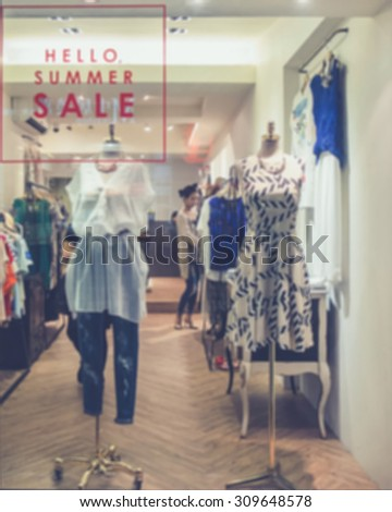 De focused/Blur image of boutique window with dressed mannequins. Boutique display window with mannequins in fashionable dresses.  - stock photo