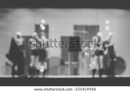 De focused/Blur image of boutique window with dressed mannequins. Boutique display window with mannequins in fashionable dresses.Black and white image. - stock photo
